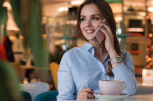 Woman sitting in coffee shop while on cellphone